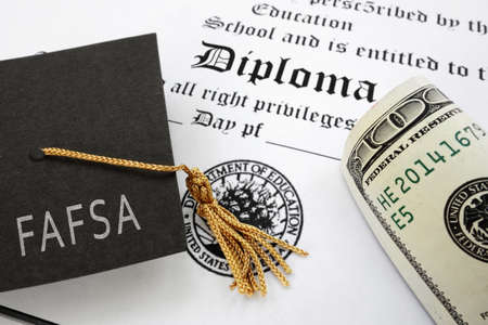 Photo pour FAFSA (Free Application for Federal Student Aid) text on graduation cap with diploma and money -- financial aid concept - image libre de droit
