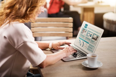 World news. Cropped picture of content businesswoman sitting at the table with cup of coffee and using a laptop in a cafe to read some news
