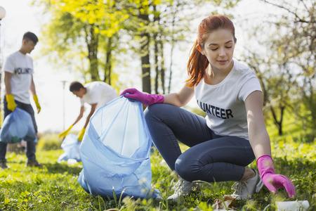 Photo pour Community project. Beautiful female volunteer looking down while gathering rubbish - image libre de droit