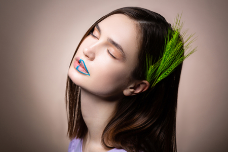 Photo for Nature time. Young model with natural makeup and blue lines on lips having spikelet in her dark straight hair - Royalty Free Image