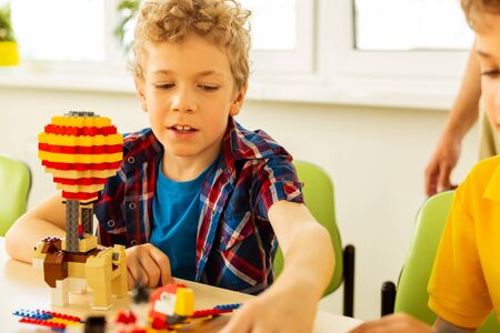 Foto de Constructing toys. Cute blonde boy taking some details from the constructor set while constructing toys - Imagen libre de derechos