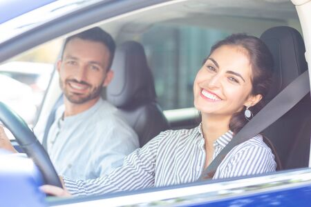 Photo pour Wife smiling broadly. Beaming wife smiling broadly while driving car of her handsome bearded husband - image libre de droit