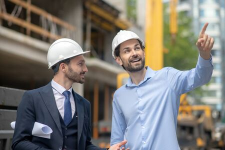 Photo for Building site. Foreman pointing his hand, showing something to building supervisor - Royalty Free Image