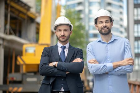 Photo for Building site. Foreman and building supervisor standing with folded arms on the building site - Royalty Free Image