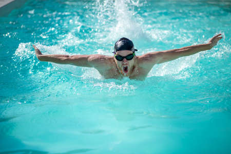 Photo pour Swimmer, inhale. Swimming swimmer on his chest, head and shoulders above water, mouth is open, his arms are extended to sides - image libre de droit