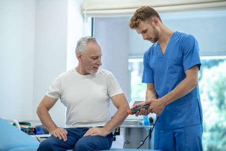 Photo pour Ultrasound treatment. Gray-haired male patient sitting on coach, receiving ultrasound elbow treatment - image libre de droit