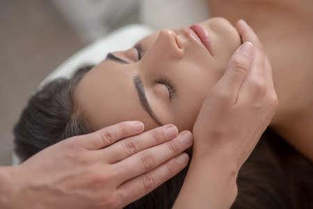 Photo pour Face massage. Professional massage therapist massaging young womans face - image libre de droit