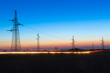 Photo for Pylons and electrical power lines at dusk with traffic lights in front - Royalty Free Image