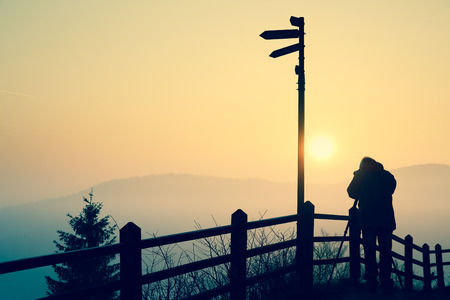 Silhouette of a photographer taking photos of an amazing sun at the top of a hill.