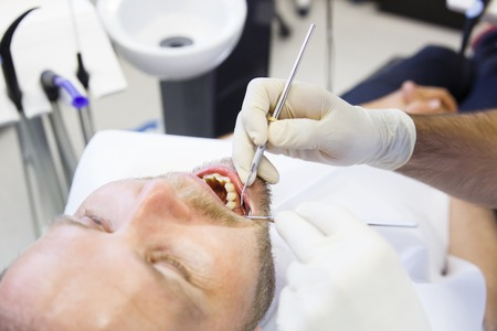 Patient in dental office, having a comprehensive examination done on regular checkup, checking for caries and periodontal disease. Oral hygiene, dental care, preventive procedures concept.