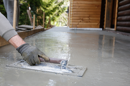 Photo pour Mason leveling and screeding concrete floor base with square trowel in front of the house. - image libre de droit