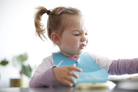 Little girl toddler picking her food, making faces. Childhood problems, picky eater, eating habits, terrible two concept.