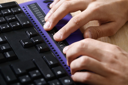 Photo pour Blind person using computer with braille computer display and a computer keyboard. Blindness aid, visual impairment, independent life concept. - image libre de droit