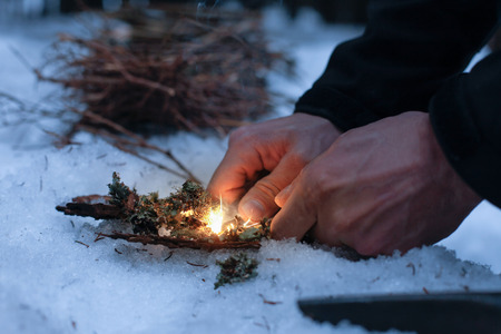 Photo pour Man lighting a fire in a dark winter forest, preparing for an overnight sleep in nature, warming himself with DIY fire. Adventure, scouting, survival concept. - image libre de droit