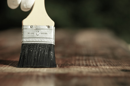 Paintbrush sliding over wooden surface, protecting wood for exterior influences, weathering, insects and fungus. Carpentry, woodwork, home improvement, do-it-yourself concept with copy space.