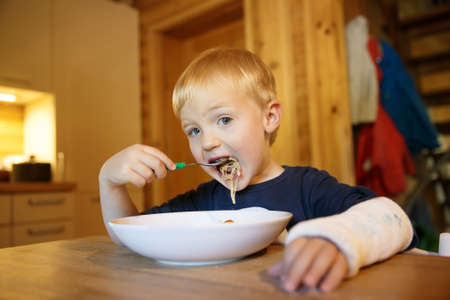 Photo pour Little boy with a broken wrist eating at the table. Boy with a plaster on his hand. - image libre de droit