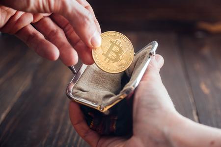 Man hand putting bitcoin into wallet. Bitcoin symbol, golden coin