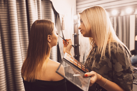 make up artist doing professional make up of young woman.の写真素材