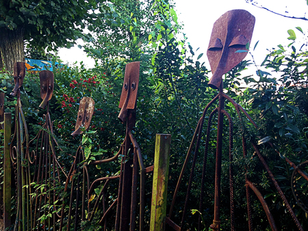 A metal, rusty face statues, sculptures on the garden.