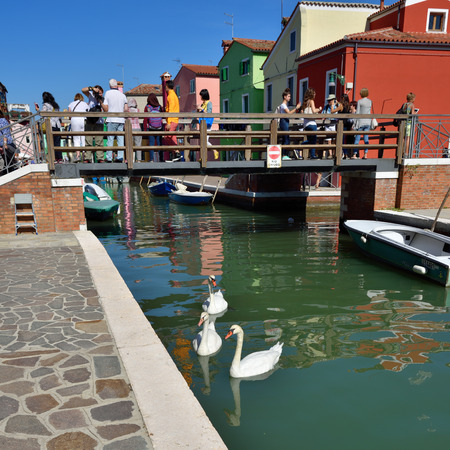 BURANO - SEP 23, 2014: Tourists from all the World are walking on the bridge inl famous Burano island, Venice. Landmark of Veneto region, Italy