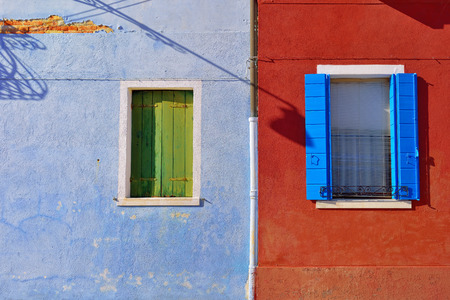 Burano island, Venice. Windows with color shutter on vivid plastered facade at sunset light. Colorful houses island and landmark of Veneto region, Italy