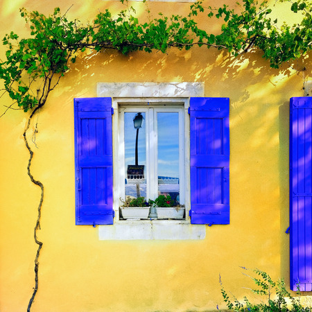 Open window with lavender color wooden shutters  on an ocher color plastered wall on a sunny day. Bonnieux village, Provence, France