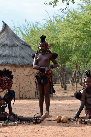 KAMANJAB, NAMIBIA - FEB 1, 2016: Unidentified Himba women with the typical necklace and hairstyle shown in himba tribe village