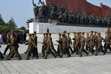 Photo for Pyongyang, North Korea - May 1, 2019: A company of soldiers marching along Pyongyang street against the Mansudae monument. Mansu hill - Royalty Free Image