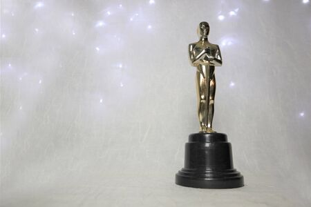 Photo pour The golden statue of Oscar on a white background, with illumination around a prestigious figure. Success and victory concept - image libre de droit