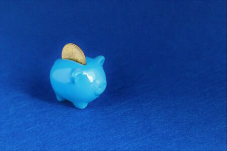 Photo for Blue Piggy bank with coin in trendy color of year 2020 on classic blue background. Saving investment, financial money, banking concept. Copy space. - Royalty Free Image