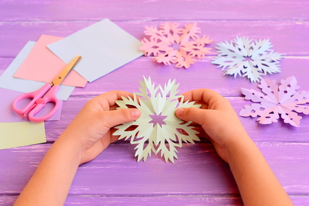 Child holds a paper snowflake in hands. Child shows snowflake decoration. Colored paper, scissors, snowflakes crafts on wooden background. How to make simple structures from a paper. Kids winter art