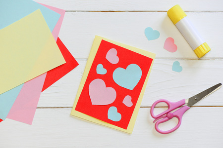 Foto de Valentines day or Mothers day card with pink and blue hearts, scissors, glue stick, colored paper sheets on a wooden table. Easy art and craft with paper for kids. Top view - Imagen libre de derechos