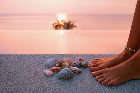 Photo pour close up of woman hands and seashells at the pool at resort at sunset - image libre de droit