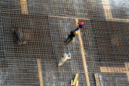 Photo pour Bird's eye view at workers in helmets on a heavy reinforced ceiling - image libre de droit