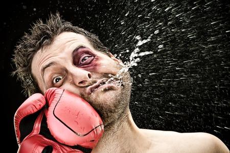 Foto de silly boxer man takes a punch in the face isolated on black.funny concept portrait - Imagen libre de derechos