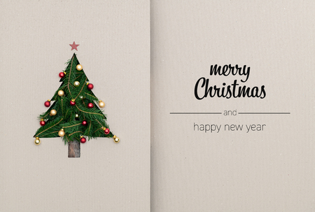 Foto de Merry Christmas and happy new year greetings in vertical top view cardboard with natural eco decorated christmas tree pine.Ecology concept.Xmas winter holiday season social media card background - Imagen libre de derechos