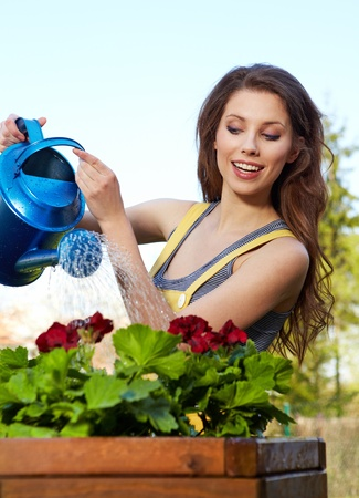 Cheerful girl watering flowers