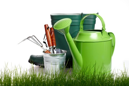 Garden tools and watering can with grass on white