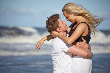 Close up portrait of romantic kiss on beach.