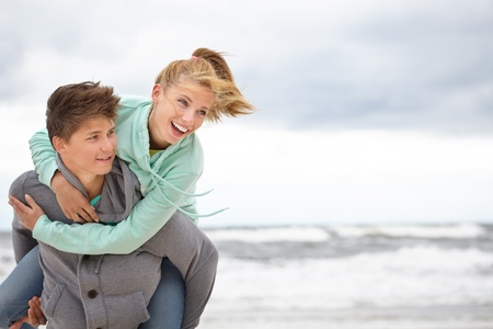 Couple embracing and having fun wearing warm clothes outside on coast behind blue sky