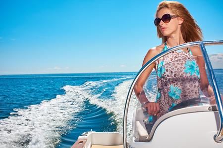 Photo pour Summer vacation - young woman driving a motor boat - image libre de droit
