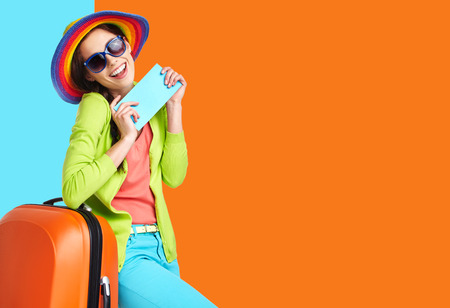 Photo pour Woman tourist with travel suitcase and blue boarding pass, isolated on summer backgroud - image libre de droit