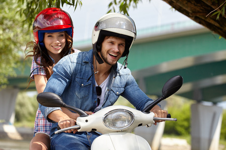 Photo for Cheerful couple riding vintage scooter - Royalty Free Image