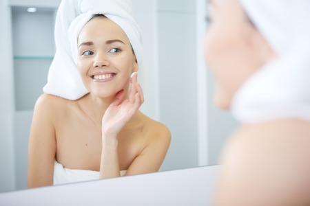 Photo pour Woman applying facial moisturizing cream. - image libre de droit