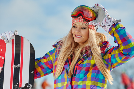 Happy young woman looking away while holding snowboard in snowの写真素材