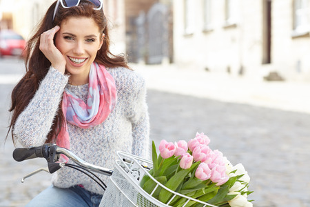 Foto de Young beautiful woman dressed in pastel on bicycle, pink and white tulips in a basket, spring outdoor. - Imagen libre de derechos