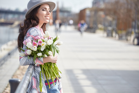 Photo pour Beautiful modern young woman in springtime. Woman with bouquet of tulips - image libre de droit