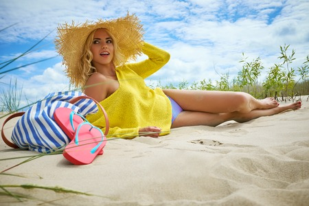 Beach woman funky happy and colorful wearing beach hat having summer fun during travel holidays vacation. trendy cool hipster woman in bikini lying in the sand.
