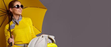 Foto de Fashion  woman with yellow umbrella and suitcase. banner concept - Imagen libre de derechos