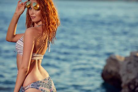 Foto de Portrait of beautiful young woman in bikini on the beach. Female model posing in swimsuit on the sea - Imagen libre de derechos